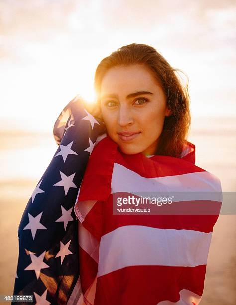 woman with american flag during sunset - american flag ocean stock pictures, royalty-free photos & images