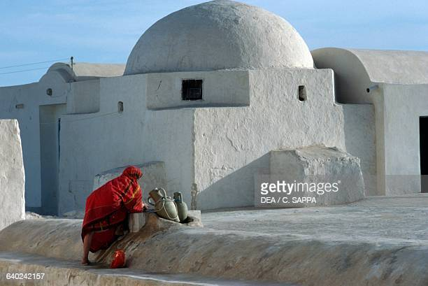 Woman with amphoras at the mosque in El May Djerba Tunisia