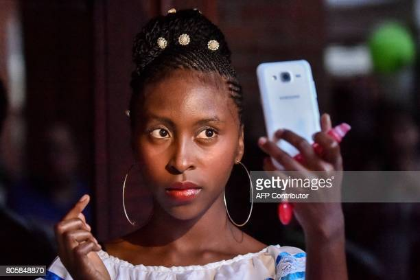 A woman with an AfroColombian hairstyle takes a selfie during the 13th contest of Afro hairdressers Tejiendo Esperanzas in Cali Valle del Cauca...