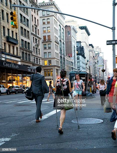 Woman with an amputated leg walks with the aid of crutches down lower Fifth Avenue