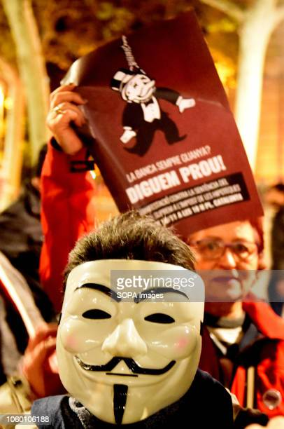 A woman with an Anonymous mask and in the background a placard saying 'Banking always wins enough is enough' are seen during the demonstration...