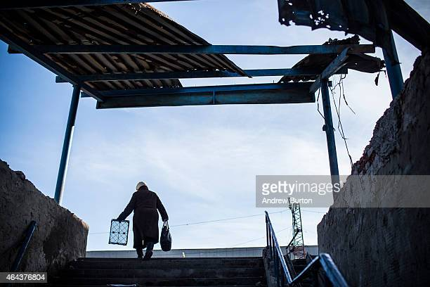 Woman with an empty basket walks through town as Russian backed rebels donate food, medicine and money to people on February 25, 2015 in Debaltseve,...