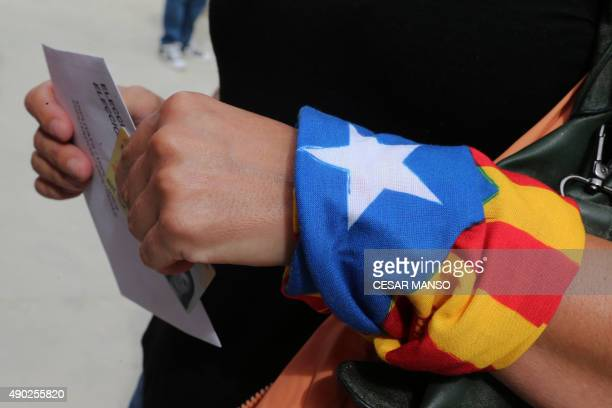 A woman with an Estelada tied to her wrist waits for casting her ballot for the regional election at a polling station in Badalona on September 27...