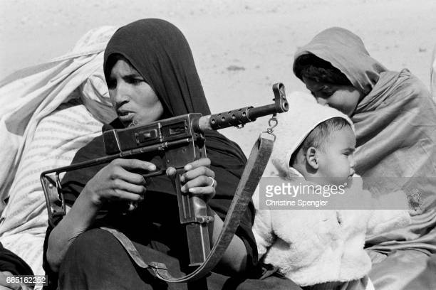 A woman with an infant holds an assault rifle during training of Polisario soldiers in Western Sahara