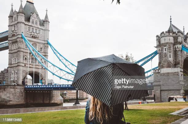 Woman with an umbrella standing by the London tower bridge