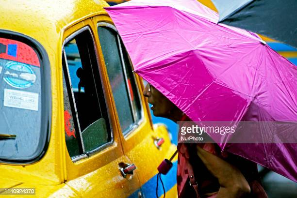 A woman with an umbrella stops a yellow taxi in Kolkata on 03 May 2019 as the cyclonic storm Fani hits the coastal places of Orissa and West Bengal...