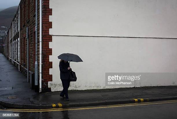 A woman with an umbrella walking down a street in the centre of the town of Port Talbot south Wales Port Talbot Tata Steel the owners of Port Talbot...