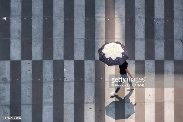 woman with an umbrella walking on a white stripes in the street - white stripes stock pictures, royalty-free photos & images