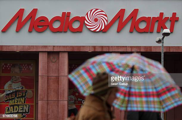 A woman with an umbrella walks by a store of German consumer electronics retail chain Media Markt on March 12 2010 in Berlin Germany Media Markt is...