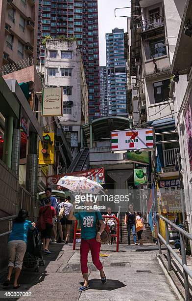 Woman with an umbrella walks down the narrow and steep street next to the Central Hong Kong escalators on May 27 in Hong Kong, China. Viewed as the...