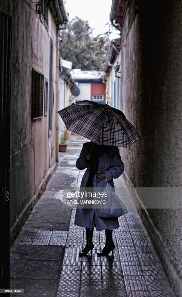 A woman with an umbrella walks in downtown Santiago July 21, 2010. Chile faces the coldest winter of the last three years, and has sustained losses that could reach USD 1,3 million in the agricultural sector. AFP PHOTO Ariel Marinkovic /