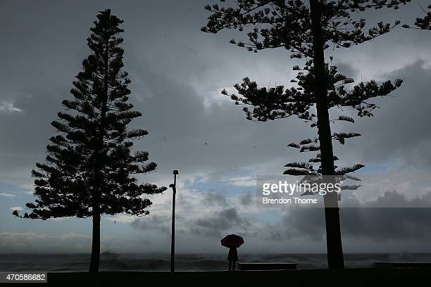 A woman with an umbrella walks on Dee Why promenade beach on April 22 2015 in Sydney Australia Three people have died and more than 200000 are still...