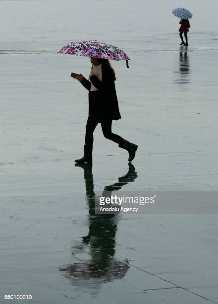 A woman with an umbrella walks over a wet floor after heavy rainfalls hit Izmir Turkey on November 27 2017 People try to prevent getting caught in...