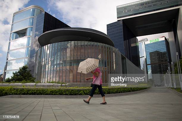 A woman with an umbrella walks past the Legislative Council Complex center which is housed in the Central Government Complex in Hong Kong China on...