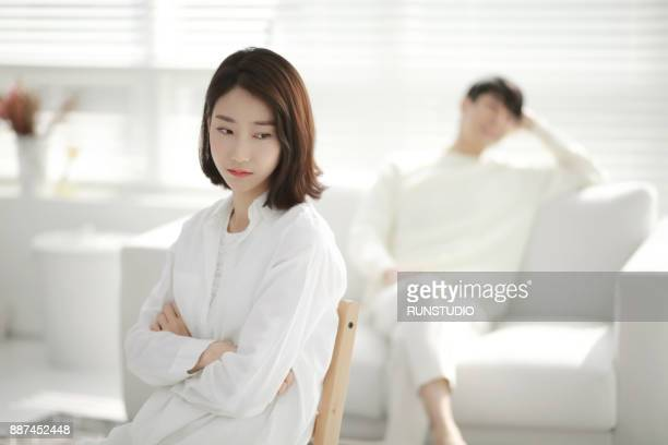 woman with angry expression, man in background - 対立 ストックフォトと画像