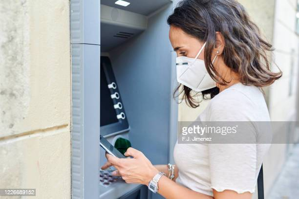 woman with antiviral mask using atm - 抗ウイルス薬 ストックフォトと画像