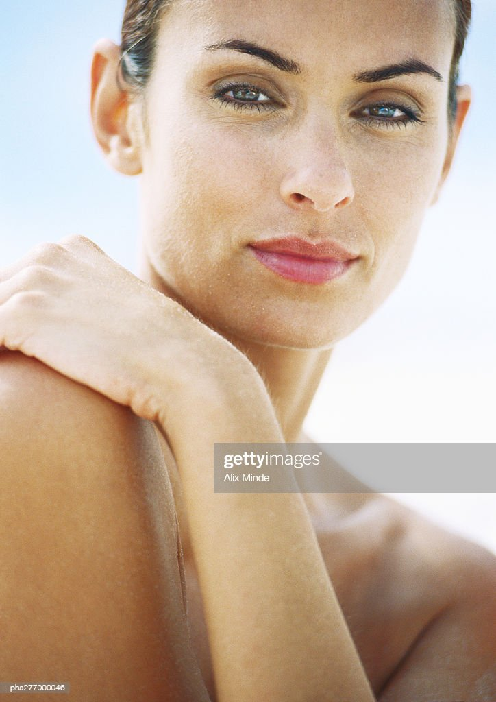 Woman with arm across chest, looking at camera, close-up : Stockfoto