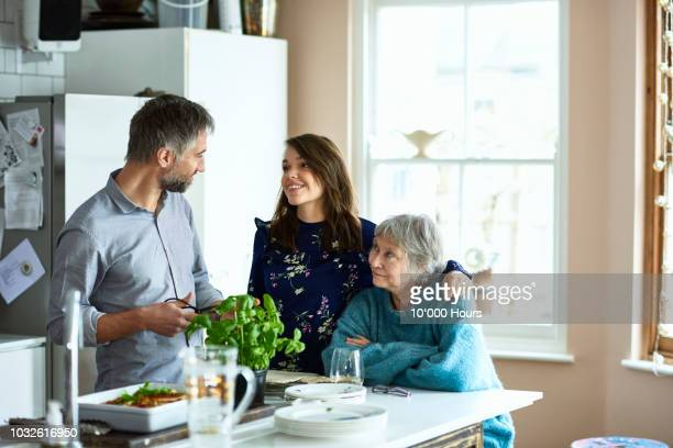 Woman with arm around mature woman looking towards man in kitchen
