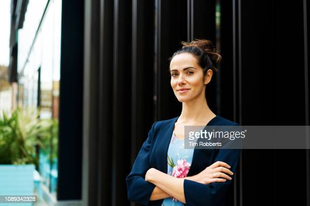 woman with arms crossed looking at camera - wall building feature stock pictures, royalty-free photos & images