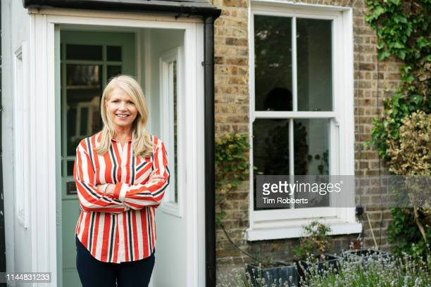 woman with arms crossed outside house - home ownership stock pictures, royalty-free photos & images