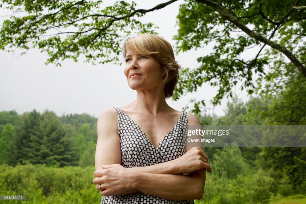 Woman with arms crossed standing against sky : Stock Photo