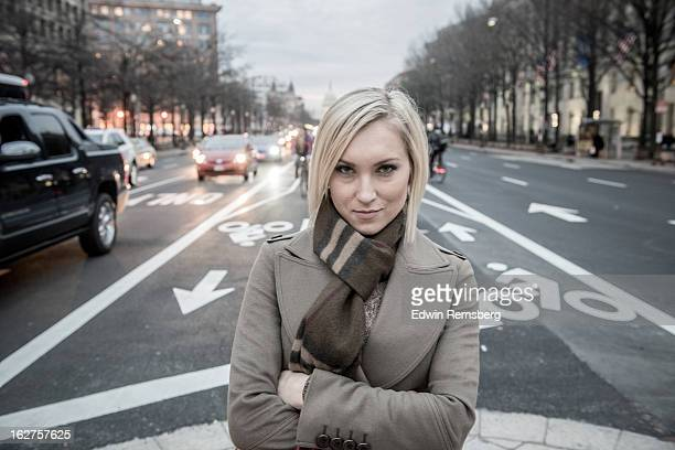 Woman with arms folded standing in bike lanes.