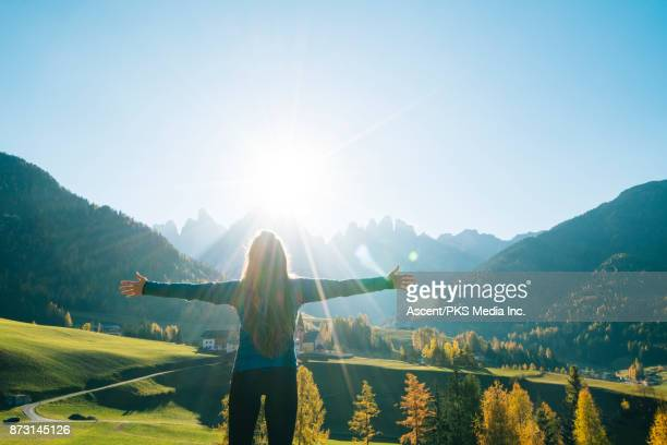 woman with arms open looks out over valley, mountains at sunrise - arms outstretched stock pictures, royalty-free photos & images
