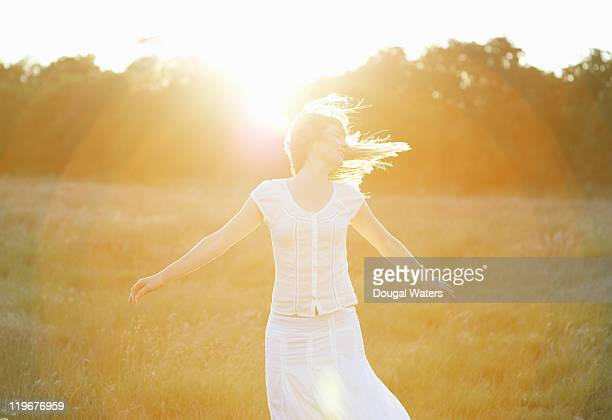 woman with arms out stretched in front of sun. - spinning stock pictures, royalty-free photos & images