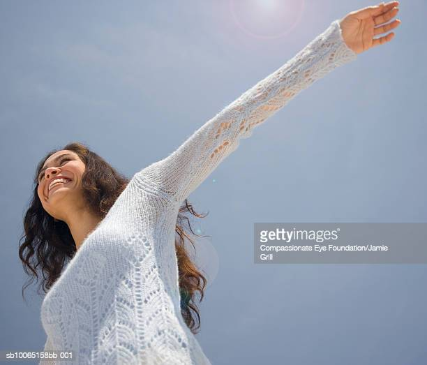 Woman with arms outstretched against sky, low angle view