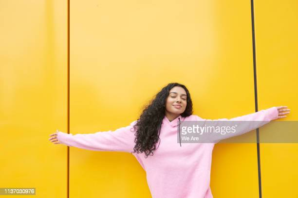 woman with arms outstretched against yellow background - mindfulness stock pictures, royalty-free photos & images