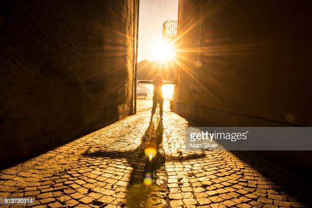 woman with arms outstretched in a narrow street with sunbeam and shadow - zonnestraal stockfoto's en -beelden