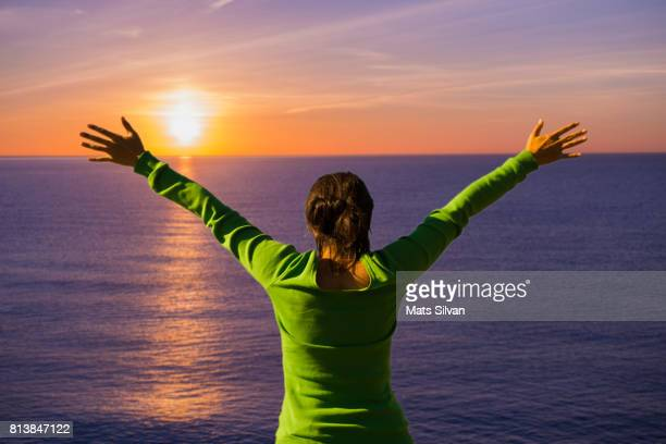 Woman with Arms Outstretched in Sunset over Mediterranean sea