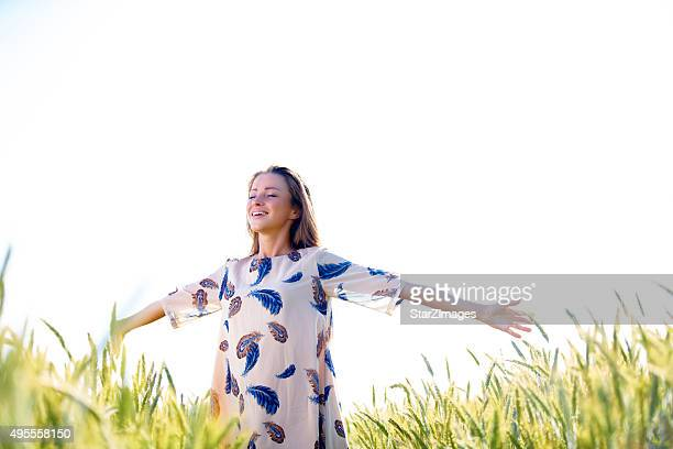 Woman with arms outstretched in wheat field