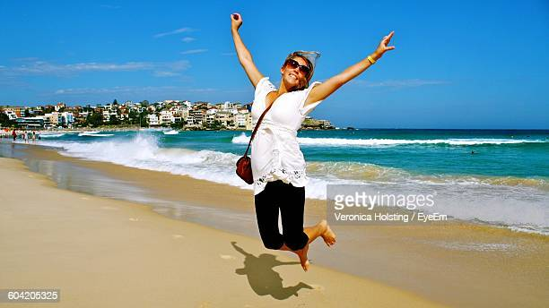 Woman With Arms Outstretched Jumping On Bondi Beach