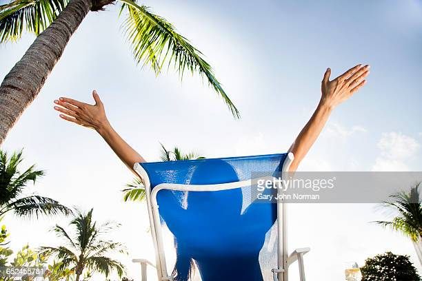 Woman with arms outstretched on sun lounger