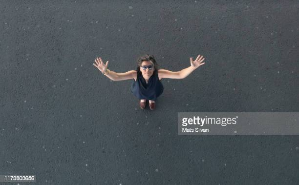 woman with arms outstretched on the street - human arm stock-fotos und bilder