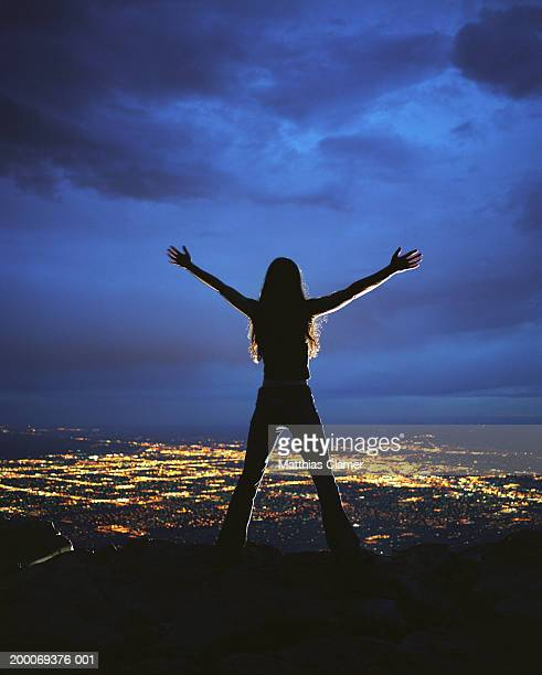 Woman with arms outstretched overlooking city at night, rear view