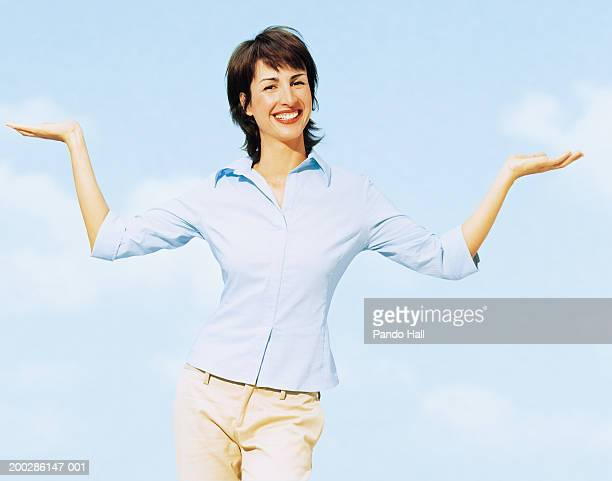 Woman with arms outstretched, palms up, smiling, portrait