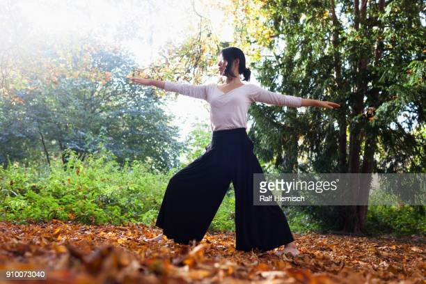 Woman with arms outstretched performing yoga while standing against trees at park