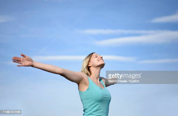 woman with arms outstretched standing against sky - ausgestreckte arme stock-fotos und bilder