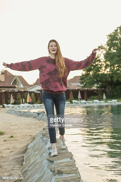 Woman with arms outstretched standing at lakeshore against clear sky