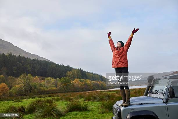 Woman with arms outstretched standing on car