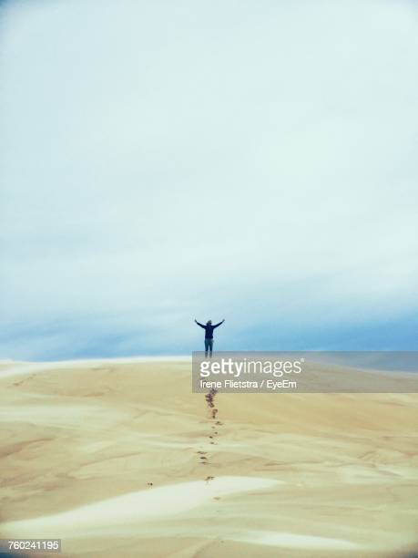 Woman With Arms Outstretched Standing On Desert Against Sky