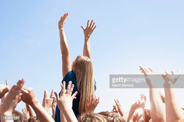 woman with arms raised above crowd - cheering stock pictures, royalty-free photos & images