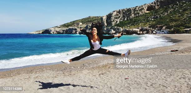 woman with arms raised and legs apart jumping at beach during sunny day - 足を開く ストックフォトと画像