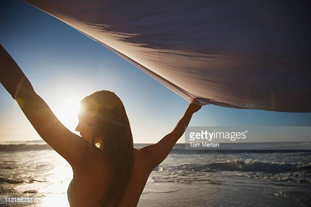 Woman with arms raised holding fabric on beach