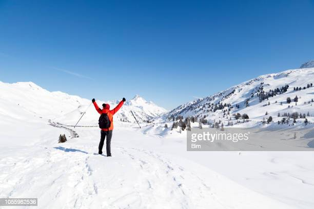 Woman With Arms Raised in Snow Covered Mountains