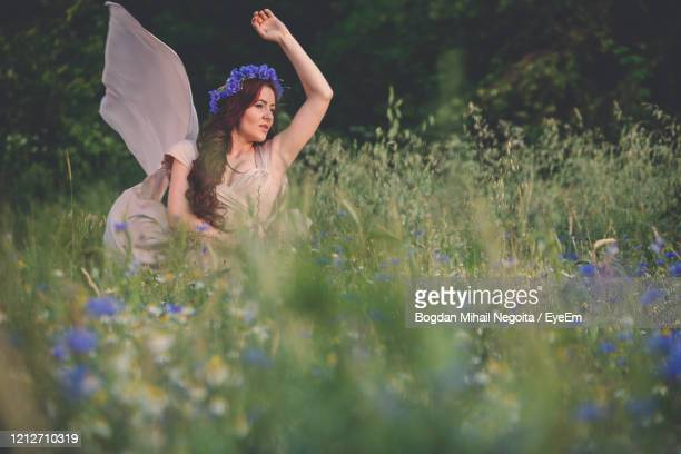 woman with arms raised on field - bogdan negoita stock pictures, royalty-free photos & images