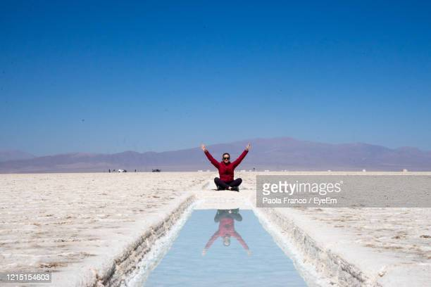 woman with arms raised reflecting in water while sitting at salt flat - サルタ州 ストックフォトと画像