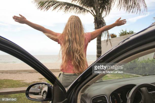 woman with arms raised sitting on parked car near the beach - southern usa stock photos and pictures
